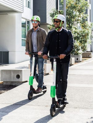 Two men riding Lime-S electric scooters.