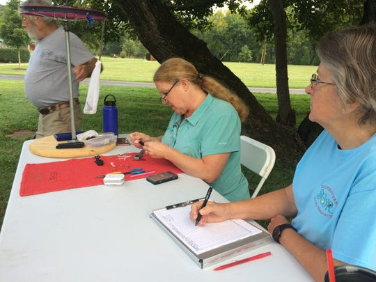 Middle, Cyndi Routledge, a federally-licensed master bird bander, records the bird's information and sets a band on its leg.