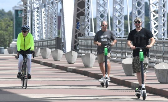People ride a Lime electric scooter on the John Seigenthaler Pedestrian Bridge on Aug. 31, 2018.