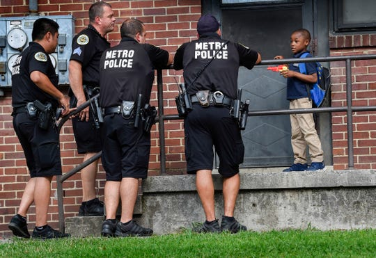 Officers with the Metro Nashville Police Department stop to talk with Marqual Goins, 7, as they walk through the Cayce Homes housing development Thursday, Aug. 30, 2018, to help establish relationships with the residents.