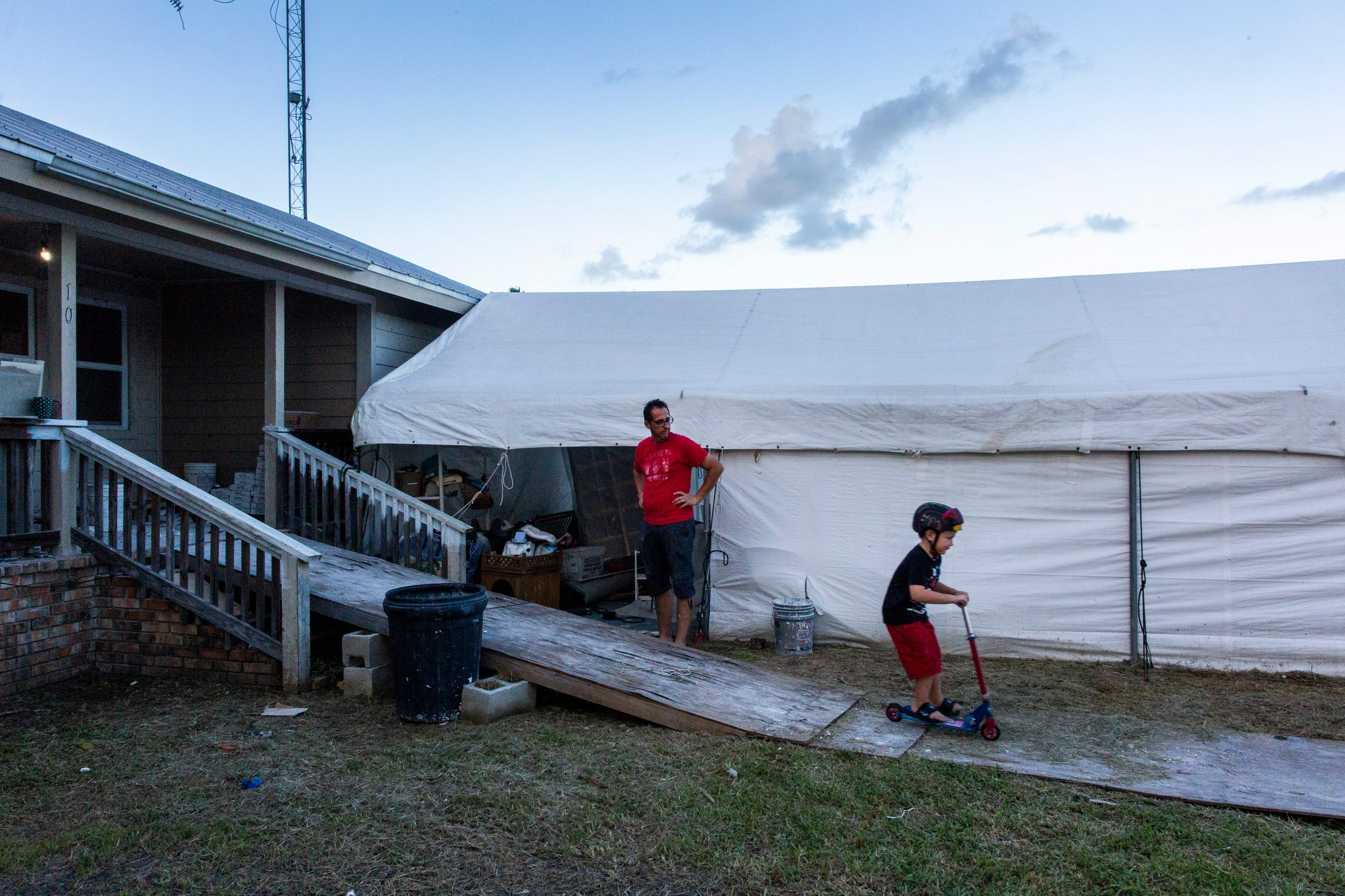 Wesley Mitchell watches over his son, Ace, as he plays outside their home in Everglades City on Thursday, Aug. 16, 2018.