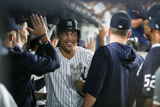 New York Yankees designated hitter Giancarlo Stanton (27) celebrates with his teammates after hitting his 300th career home run in the third inning against the Detroit Tigers at Yankee Stadium on Aug. 30, 2018.
