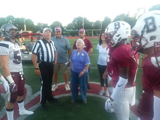 Pat Carter, the mother of Bloomfield football coach Mike Carter, tossing the coin prior to kickoff of the Nutley-Bloomfield game. Mrs. Carter was honored after retiring from the Bloomfield school system, having devoted nearly 50 years of service