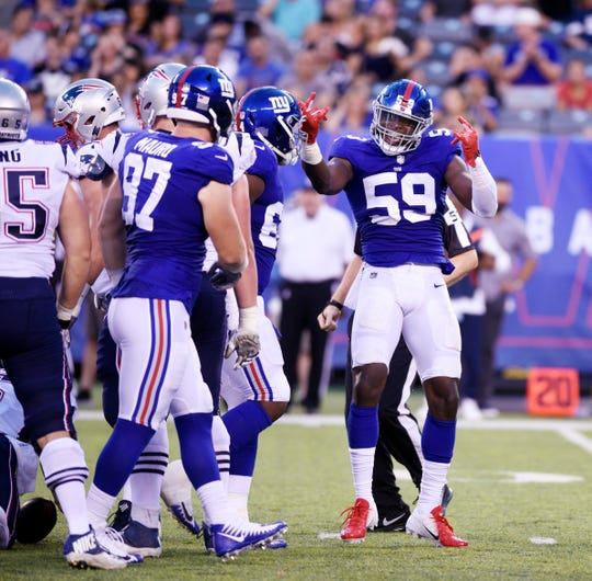 Giants vs. Patriots preseason game at MetLife Stadium in East Rutherford on Thursday, August 30, 2018. G #59 Lorenzo Carter celebrates after making a tackle in the first quarter.