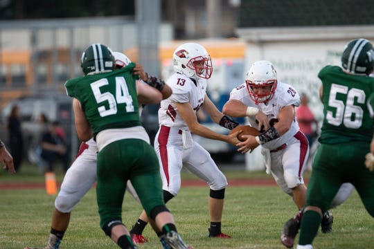 Frank Negrini (28) takes a handoff from Michael Ederhart (13).