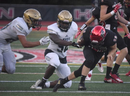 Northern Highlands' Vinny Demaria (32)  is tackled by NV/Old Tappan's Charles James (52) on Thursday as NV/OT went on to beat NH, 35-14 in the season opener for high school football in New Jersey, Aug. 30, 2018.