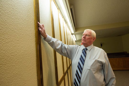 Terry Getz, owner of Getz Funeral Home in Las Cruces, points on Friday, Aug. 31, 2018 to where hooks slide out of a wall for flowers to be hung during funeral services in the home's chapel.