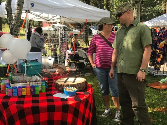 Visitors to a previous Lumberjack Festival peruse the vendors offering various items.