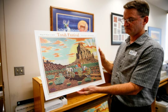"""Farmington Museum director Bart Wilsey shows this year's Totah Festival poster, a sand painting by Littleriver Simpson entitled """"Trip to the Trading Post."""" Thursday at the Farmington Museum at Gateway Park."""