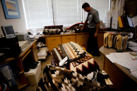Farmington Museum director Bart Wilsey looks through stacks of rugs Thursday in his office at the Farmington Museum at Gateway Park in preparation for the Totah Festival rug auction.