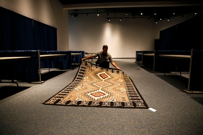 Farmington Museum director Bart Wilsey lays out a Teec Nos Pos-style rug from the 1940s Thursday at the Farmington Museum at Gateway Park. The rug will be up for auction today during the Totah Festival.