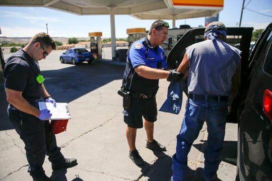 Farmington Fire Department Station One Capt. Mike Stahll and Farmington Police Department District Coordinator Ofc. Kris Chavez prepare to transport an inebriated person to the Sobering Center, Thursday, Aug. 30, 2018 shortly after making contact with the individual at the Shell gas station off West Apache Street in Farmington.