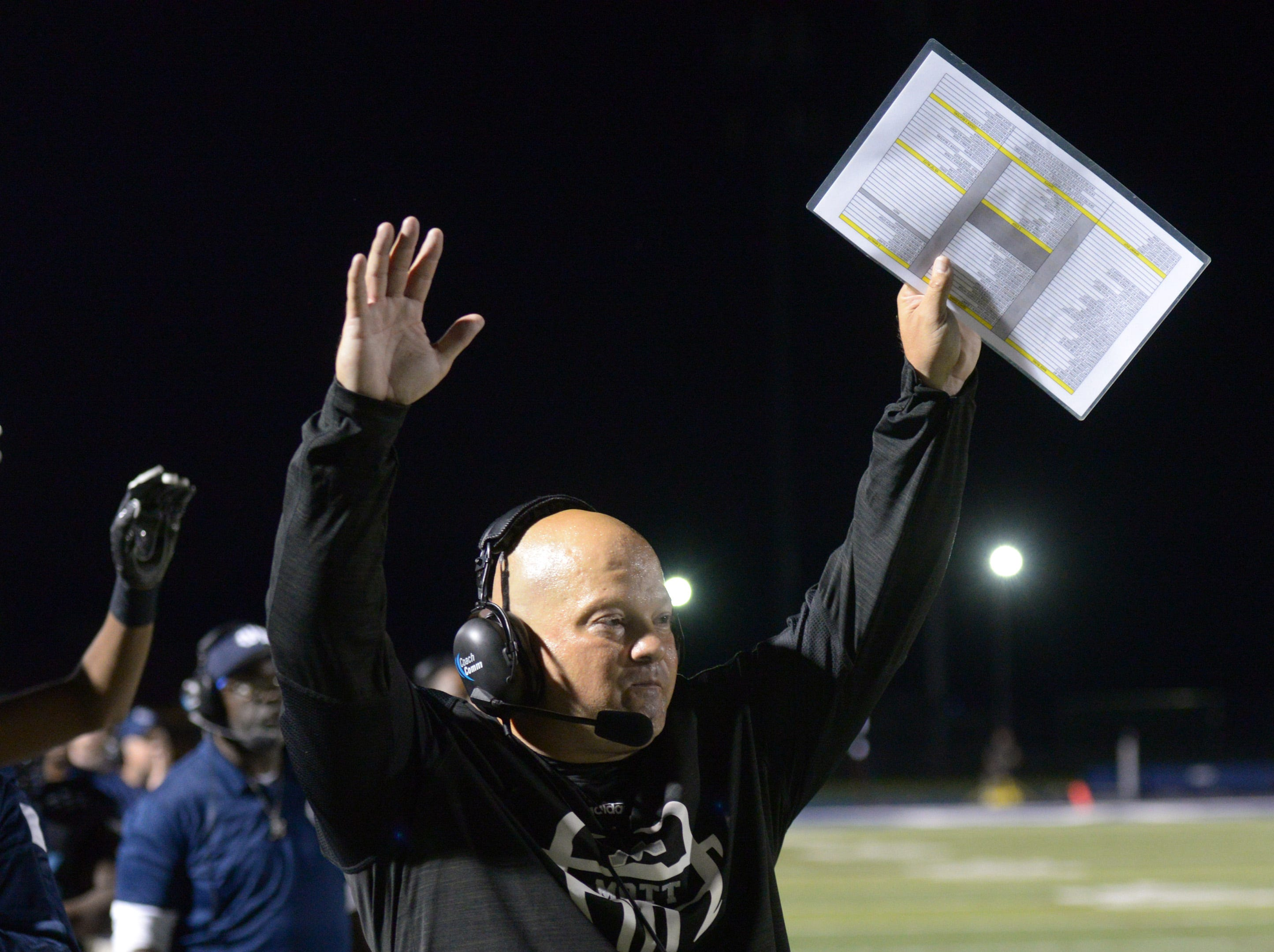 Waterford Mott coach Chris Fahr signals a TD late on the fourth quarter as his defeats Lakeland 26-19.