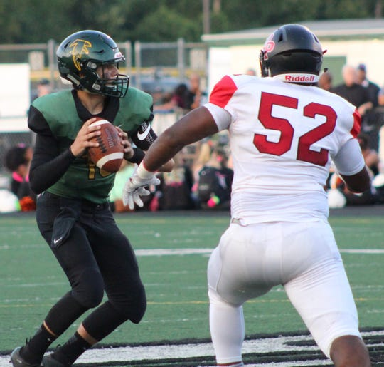 Groves quarterback Markis Alexander prepares to pass downfield despite a heavy rush by Oak Park defensive end Justin Rogers.
