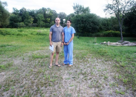 The Sherwoods stand on what used to be a grass-covered, tree-lined section of their backyard.
