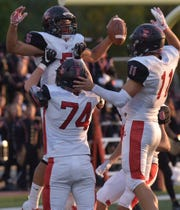 Churchill's Brendan Lowry (5) celebrates his touchdown catch with Caden McCusker (74) and Drew Alsobrooks.