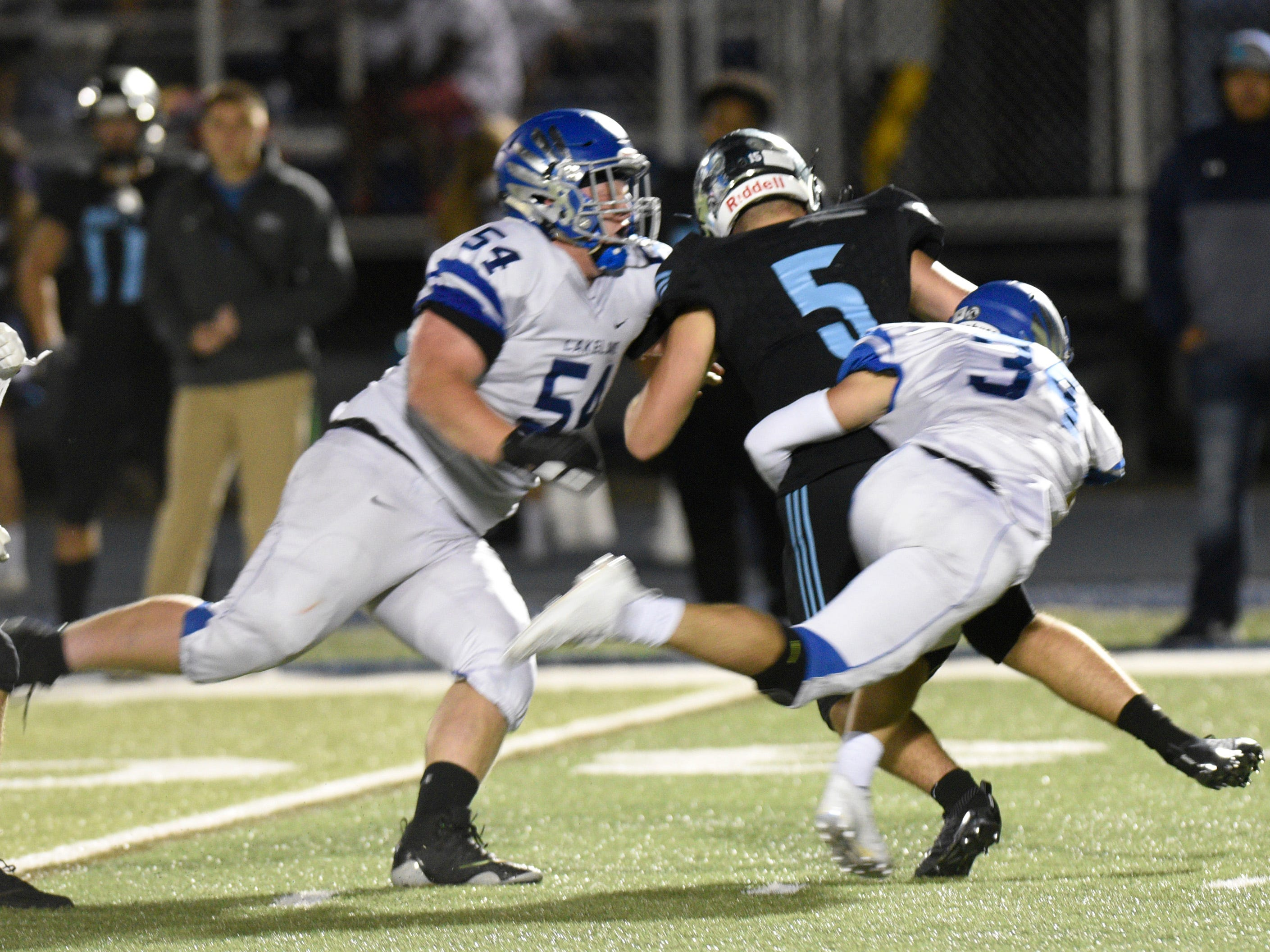 Lakeland players Ben Roberts (54) and Matt Fus sack Waterford Mott QB Matthew Castillo Jr.