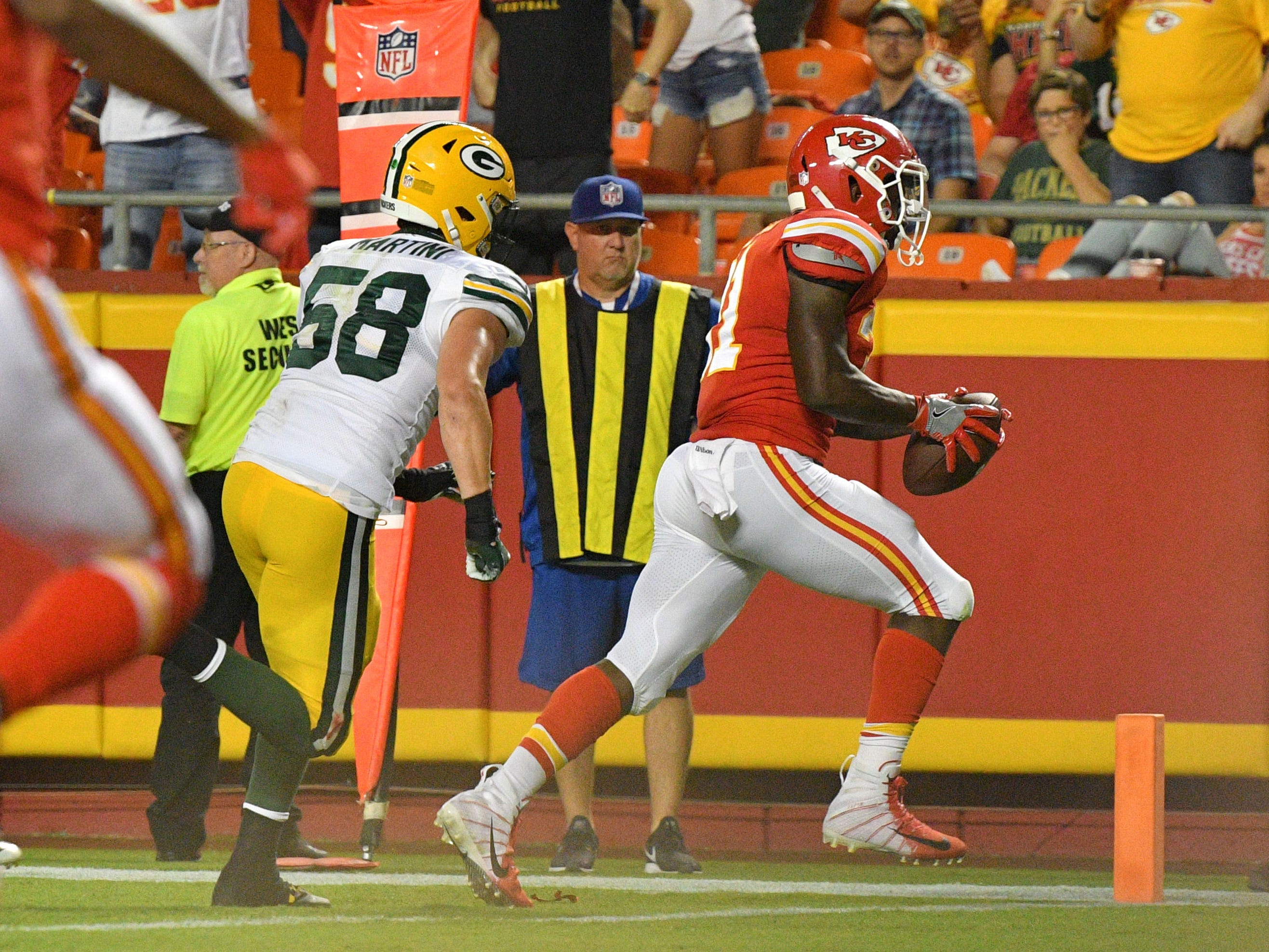Aug 30, 2018; Kansas City, MO, USA; Kansas City Chiefs running back Darrel Williams (31) scores as Green Bay Packers linebacker Greer Martini (58) chases during the first half at Arrowhead Stadium.
