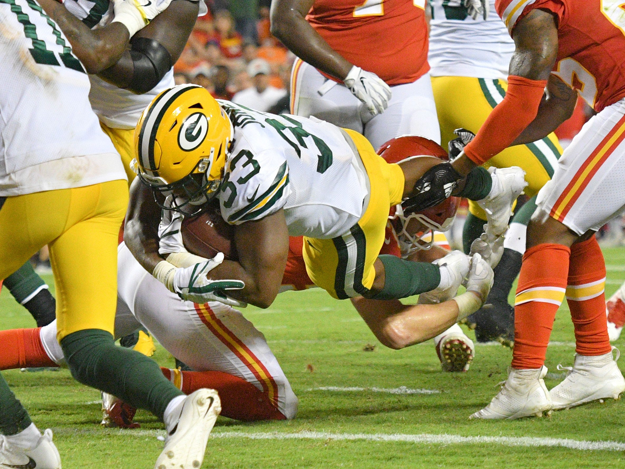 Aug 30, 2018; Kansas City, MO, USA; Green Bay Packers running back Aaron Jones (33) scores a touchdown and is tackled by Kansas City Chiefs linebacker Ben Niemann (56) during the first half at Arrowhead Stadium.