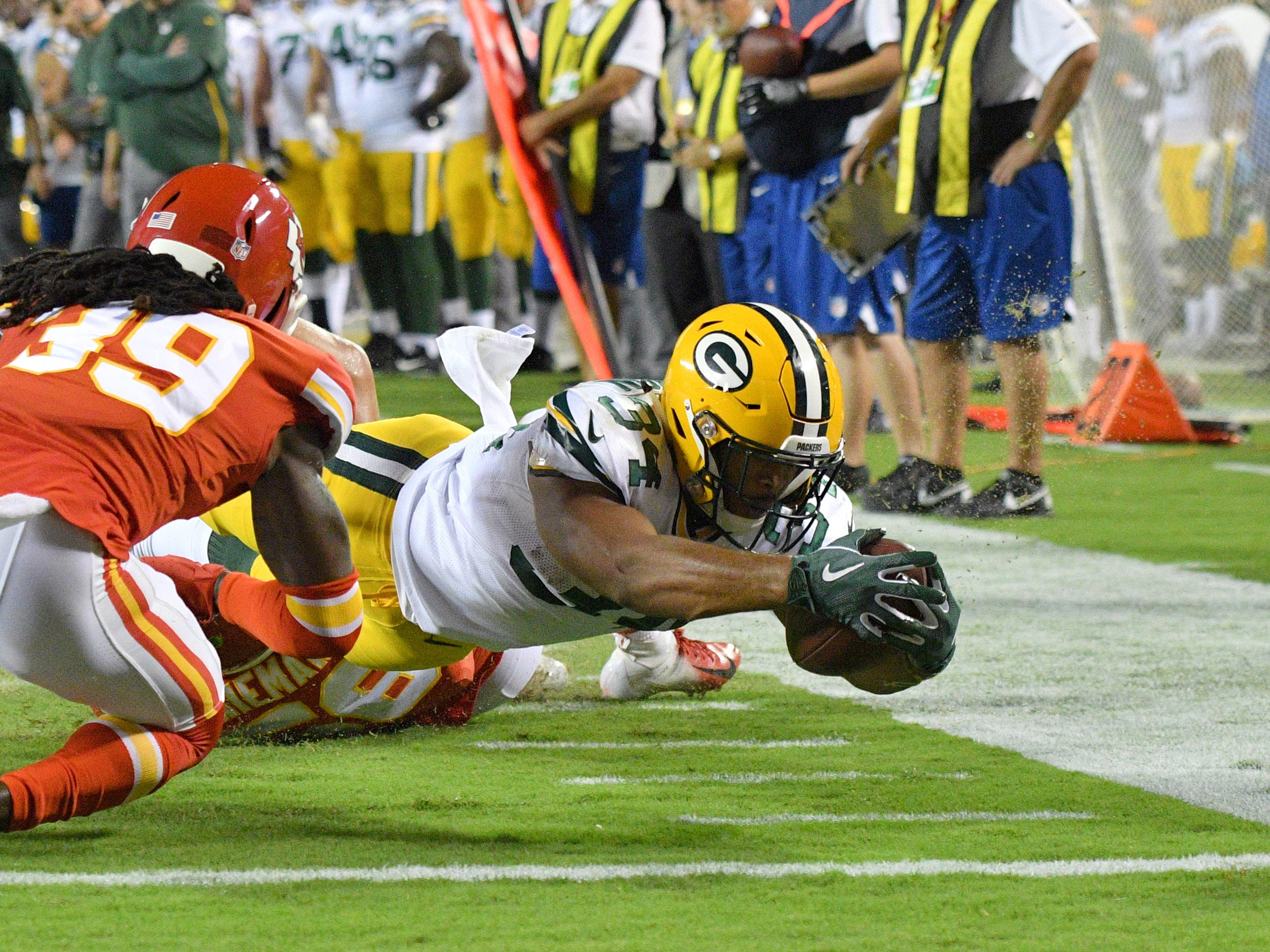 Aug 30, 2018; Kansas City, MO, USA; Green Bay Packers running back Joel Bouagnon (34) runs and is tackled by Kansas City Chiefs linebacker Ben Niemann (56) and defensive back Tremon Smith (39) during the first half at Arrowhead Stadium.