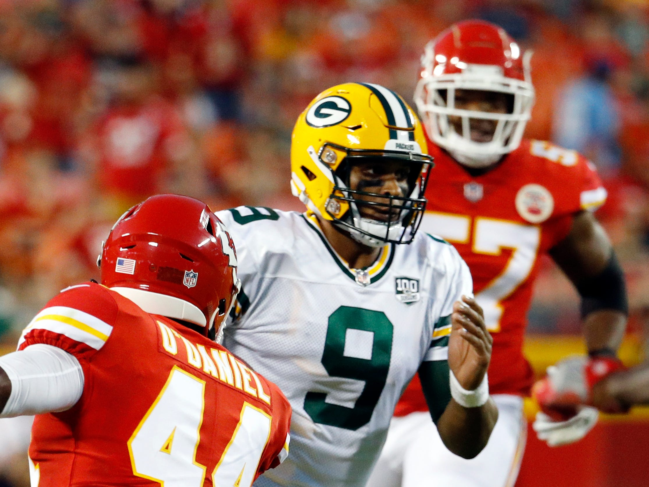 Green Bay Packers quarterback DeShone Kizer (9) runs with the ball between Kansas City Chiefs linebacker Dorian O'Daniel (44) and linebacker Breeland Speaks (57) during the first half of an NFL preseason football game in Kansas City, Mo., Thursday, Aug. 30, 2018.