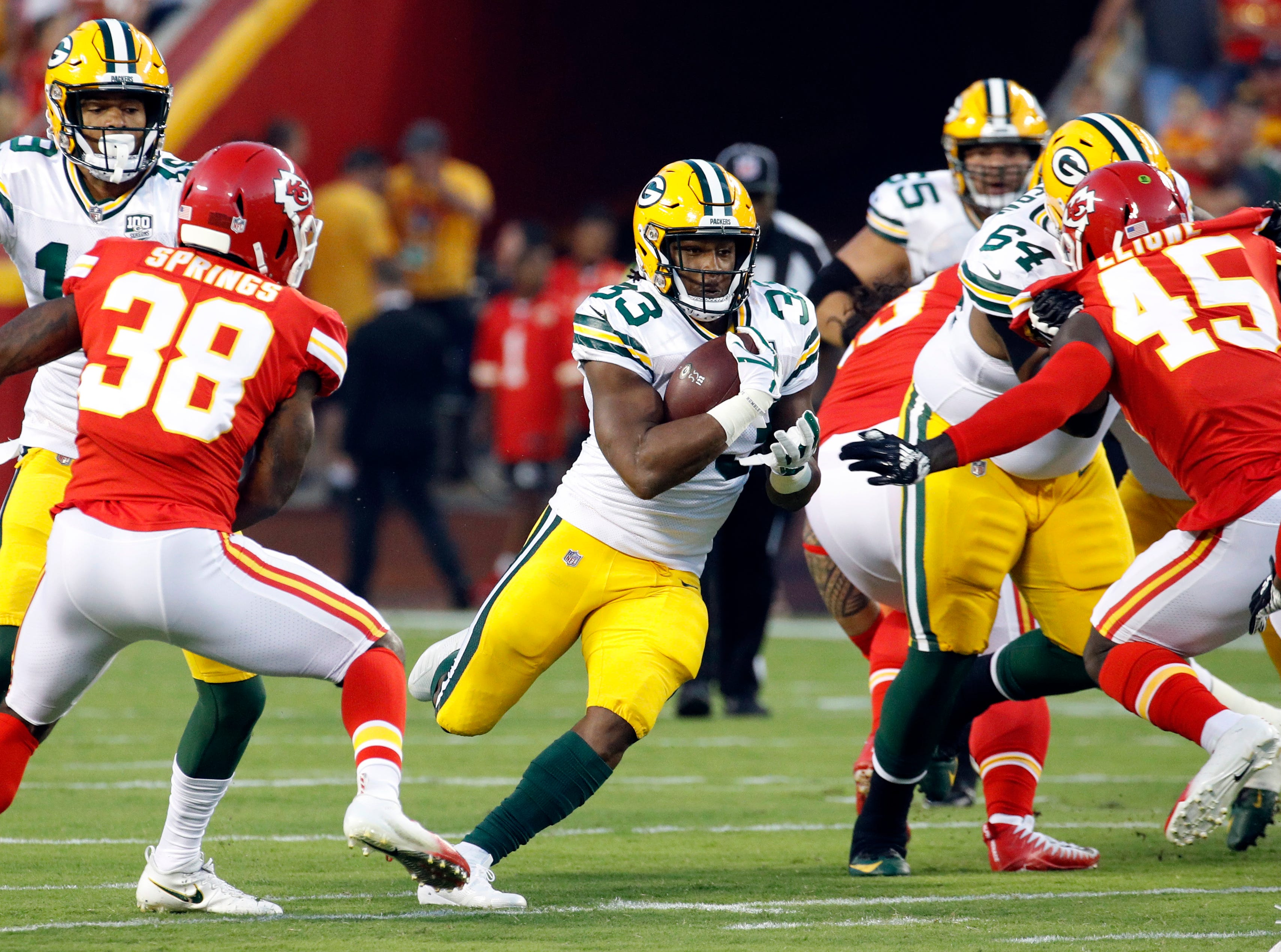 Green Bay Packers running back Aaron Jones (33) runs between Kansas City Chiefs cornerback Arrion Springs (38) and linebacker Ukeme Eligwe (45) during the first half of an NFL preseason football game in Kansas City, Mo., Thursday, Aug. 30, 2018.