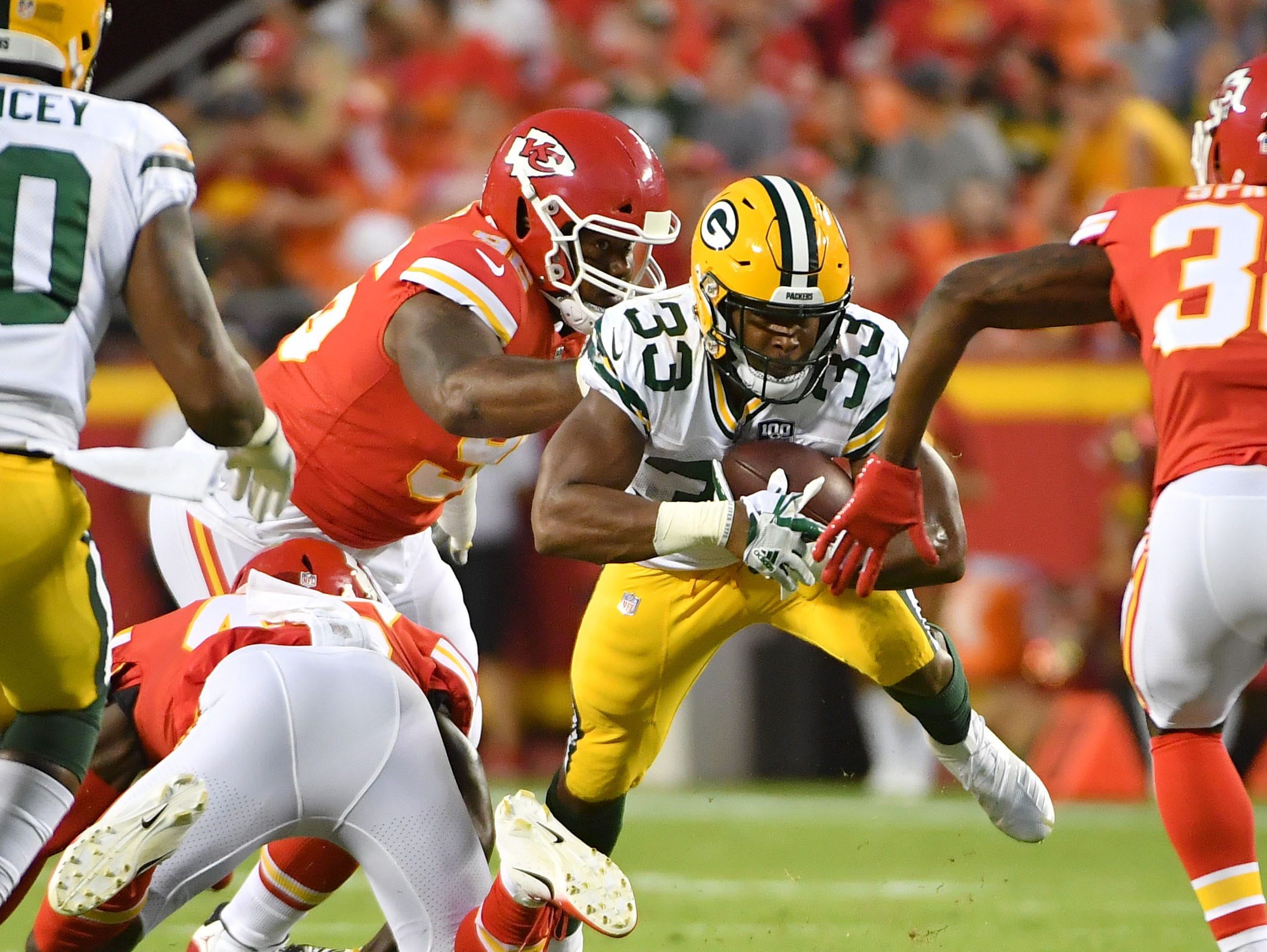 Aug 30, 2018; Kansas City, MO, USA; Green Bay Packers running back Aaron Jones (33) runs the ball and is tackled by Kansas City Chiefs defensive back Leon III McQuay (34) during the first half at Arrowhead Stadium.