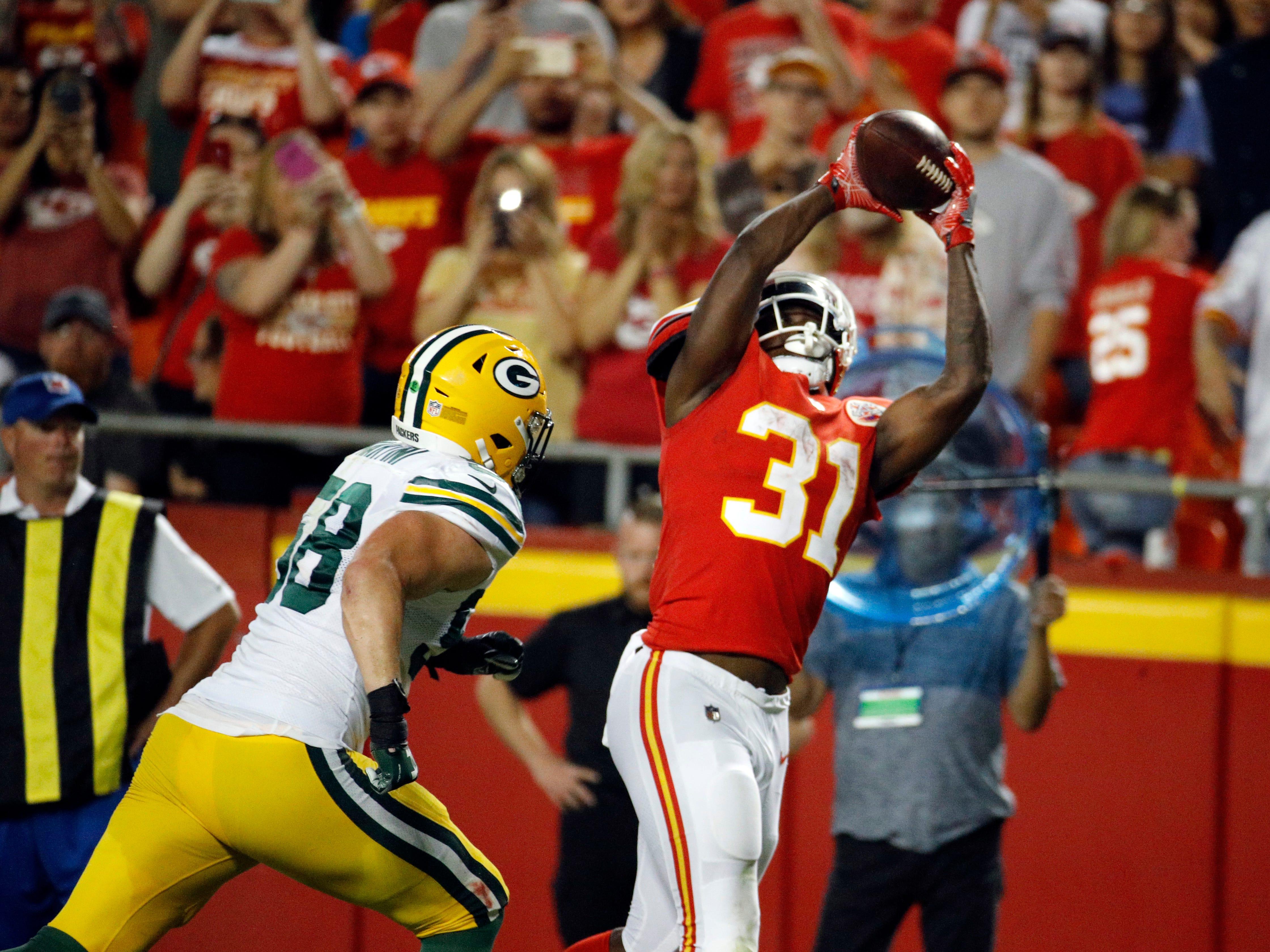 Kansas City Chiefs running back Darrel Williams (31) makes a touchdown catch against Green Bay Packers linebacker Greer Martini (58) during the first half of an NFL preseason football game in Kansas City, Mo., Thursday, Aug. 30, 2018.