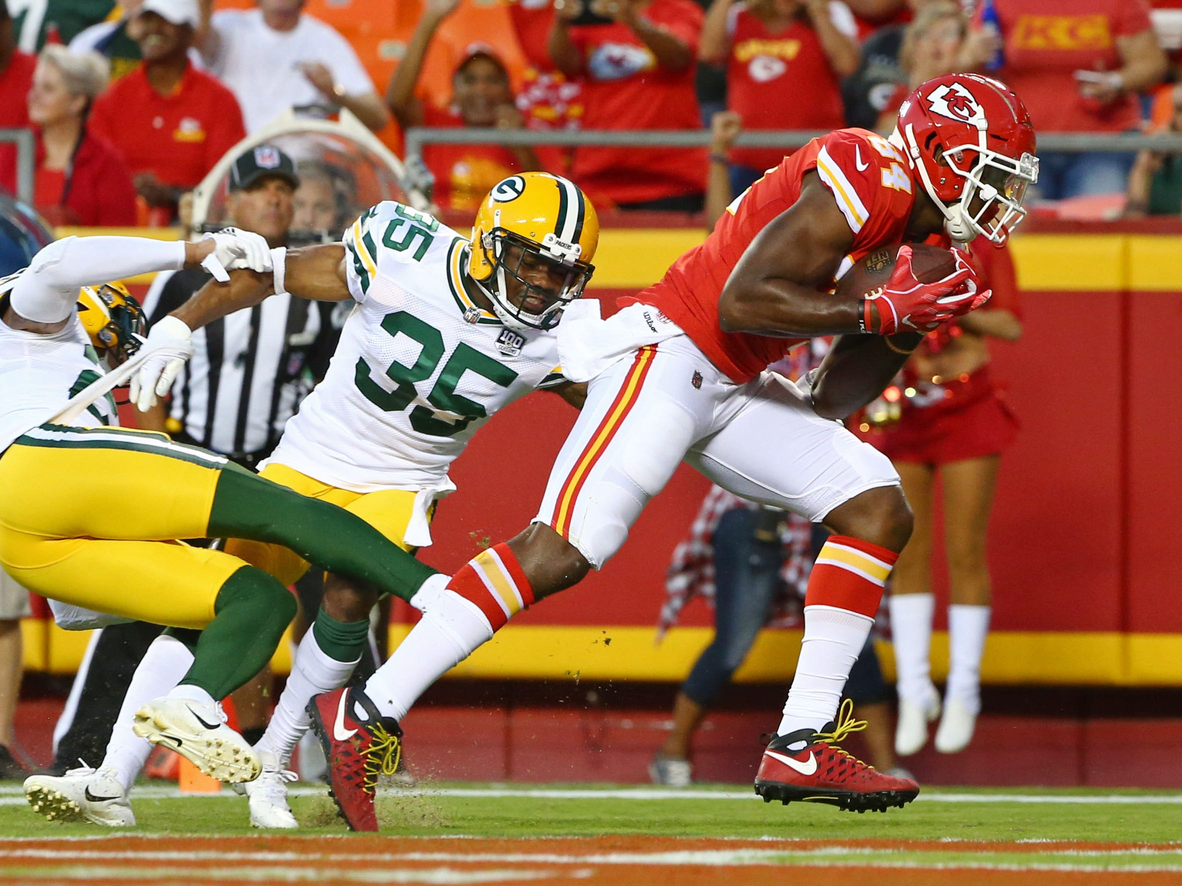 Aug 30, 2018; Kansas City, MO, USA; Kansas City Chiefs tight end Demetrius Harris (84) scores a touchdown as Green Bay Packers safeties Jermaine Whitehead (35) and  Josh Jones (27) defend in the first half at Arrowhead Stadium.