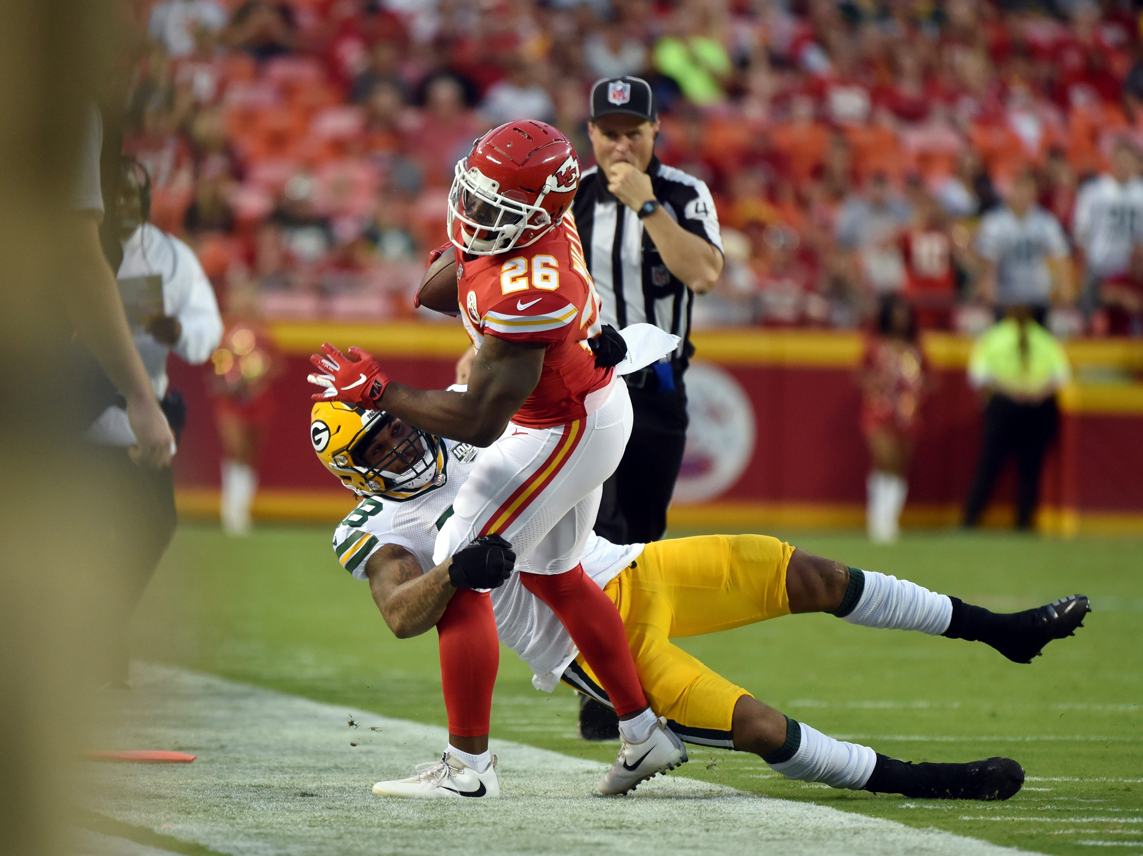 Kansas City Chiefs running back Damien Williams (26) is tackled by Green Bay Packers linebacker Antonio Morrison (48) during the first half of an NFL preseason football game in Kansas City, Mo., Thursday, Aug. 30, 2018.