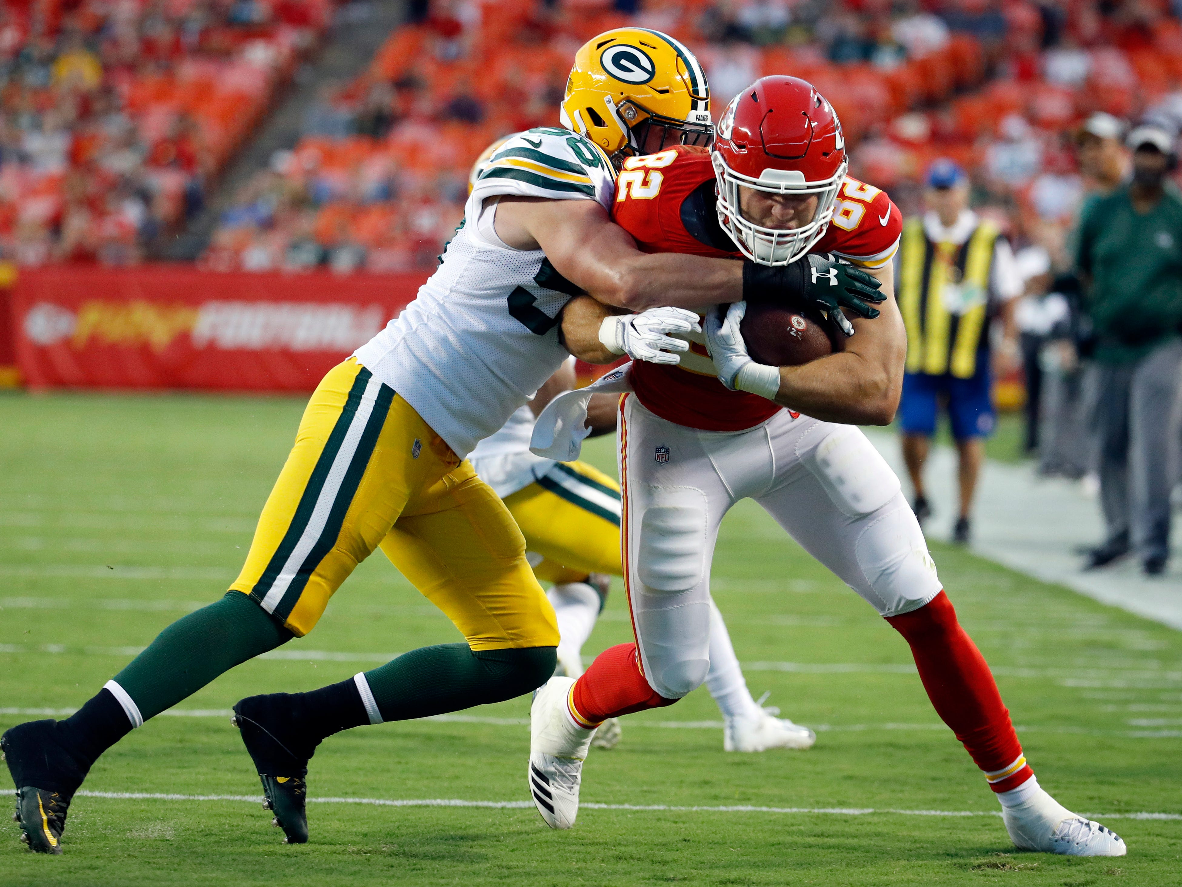 Kansas City Chiefs tight end Alex Ellis (82) is tackled by Green Bay Packers linebacker Greer Martini (58) during the first half of an NFL preseason football game in Kansas City, Mo., Thursday, Aug. 30, 2018.
