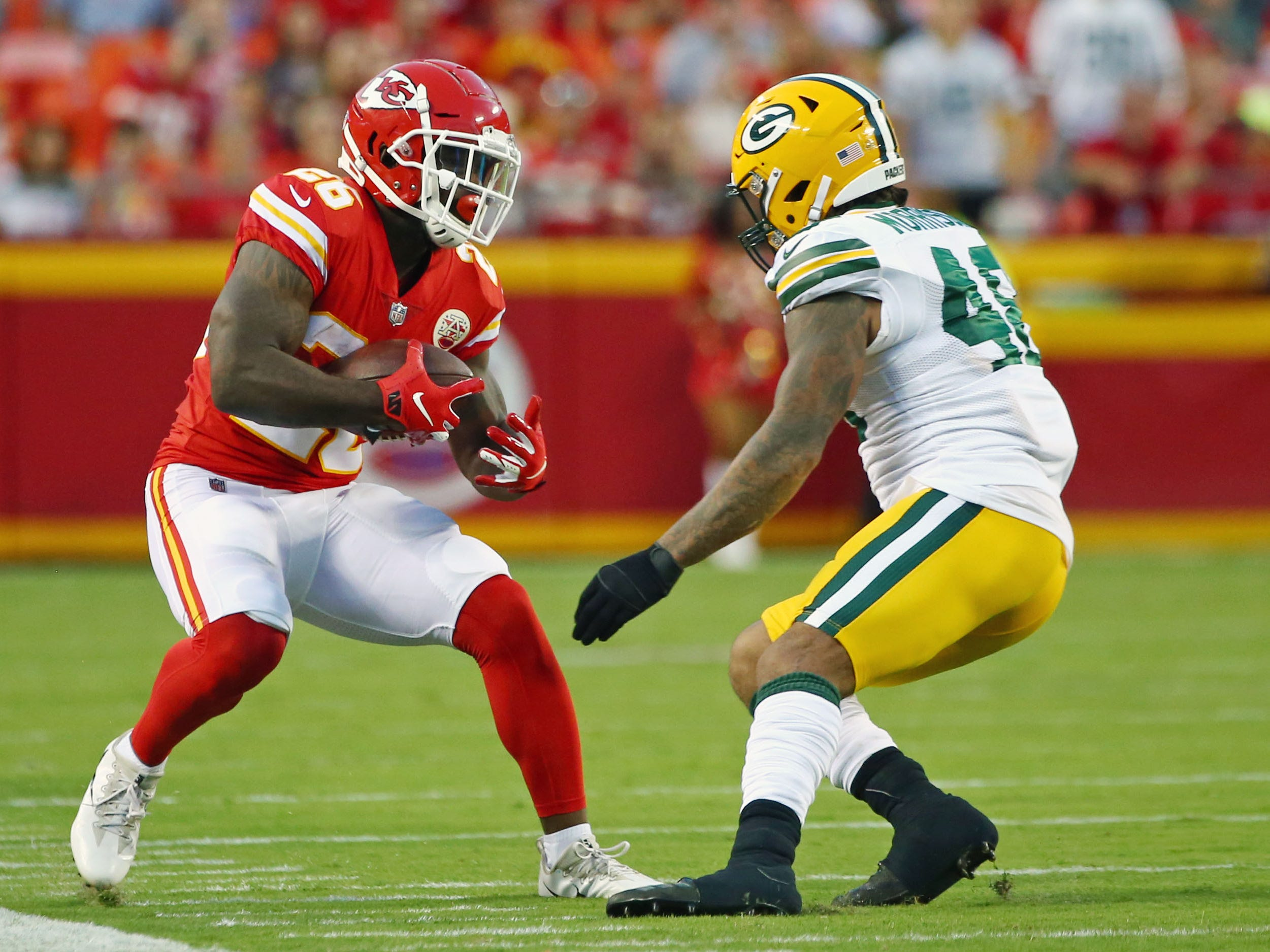 Aug 30, 2018; Kansas City, MO, USA; Kansas City Chiefs running back Damien Williams (26) runs against Green Bay Packers linebacker Antonio Morrison (48) in the first half at Arrowhead Stadium.
