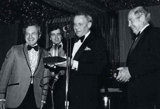 Frank Sinatra, Lloyd Maryanov, Larry Minden, Howard Wiefels at Desert Hospital function, Sinatra accepting crystal sculpture, Maryanov was mayor at the time.