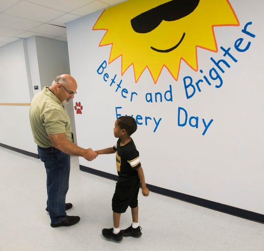Warrington Elementary School Principal, Tim Rose, greets a student in the hallway near a mural of the school's motto on Friday, Aug. 31, 2018.