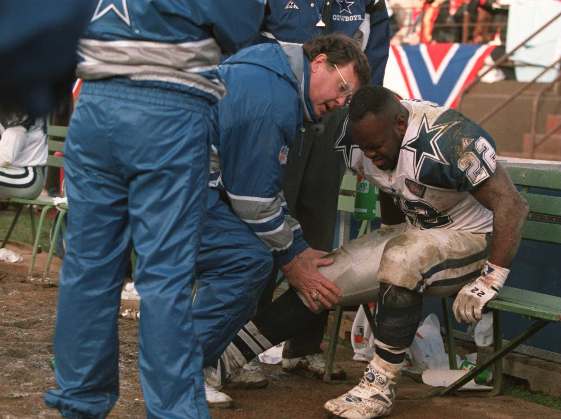 15 JAN 1995:  DALLAS RUNNING BACK EMMITT SMITH IS WORKED ON BY A DALLAS TRAINER AFTER HE PULLED HIS RIGHT HAMSTRING DURING THE 49ERS 38-28 VICTORY OVER THE DALLAS COWBOYS IN THE NFC CHAMPIONSHIP GAME AT CANDLESTICK PARK IN SAN FRANCISCO, CALIFORNIA. Manda