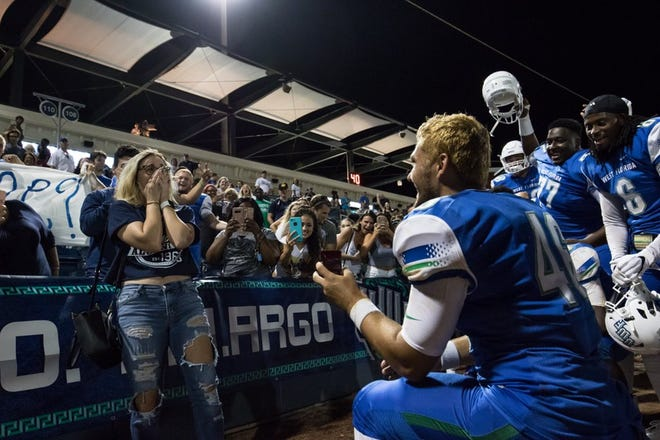 University of West Florida long snapper Austin Johnson proposes to his girlfriend, Kacey Webber, on Thursday night after the Argos' 19-9 win over No. 22 Carson-Newman.