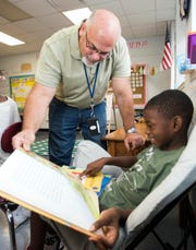 Warrington Elementary School Principal Tim Rose checks up on Malik Rhodes during his visit to his first-grade class on Friday.