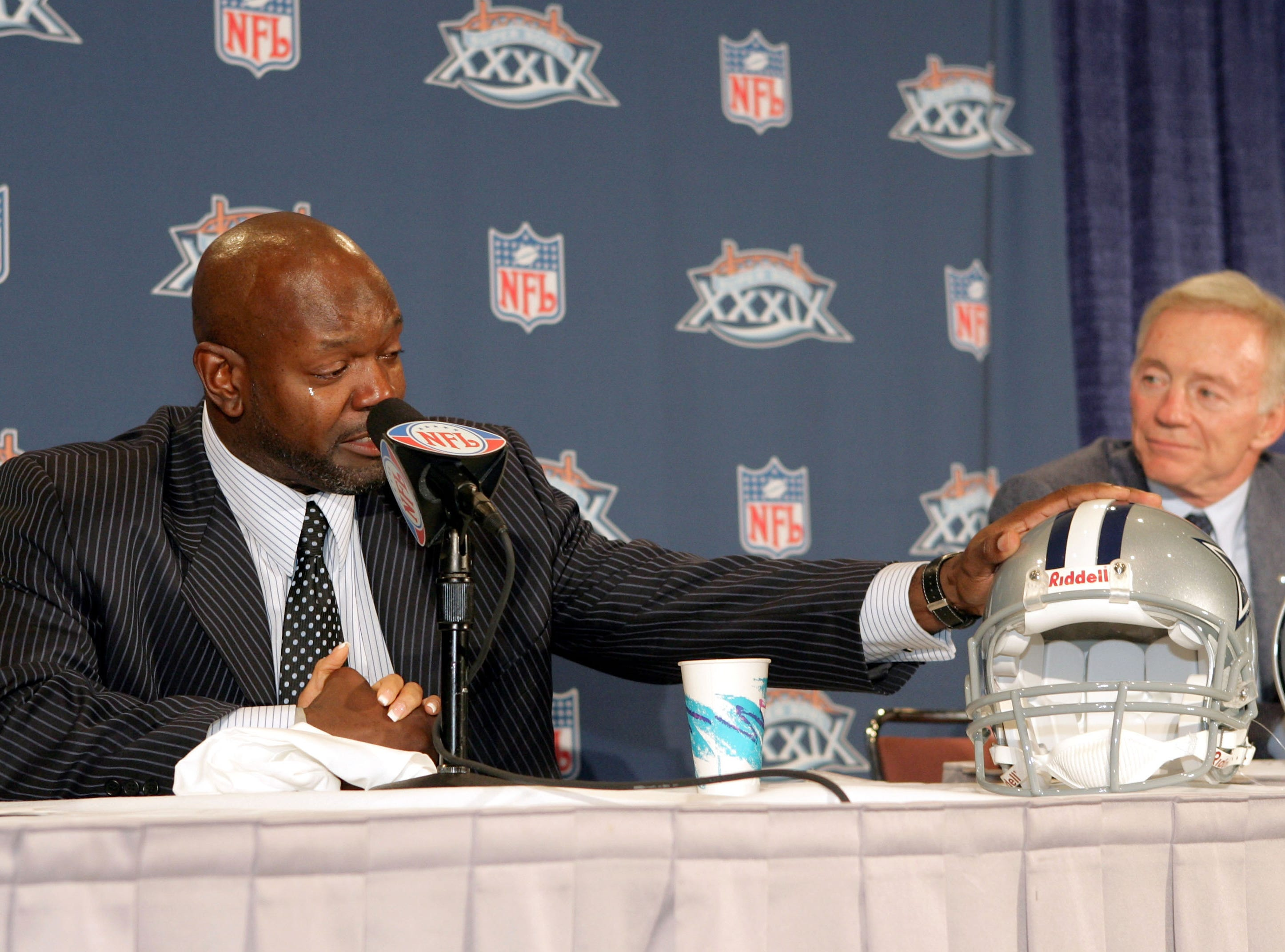 JACKSONVILLE, FL - FEBRUARY 3:  Running back Emmitt Smith becomes emotional at a press conference held to announce his retirement from the NFL after 15 years as Dallas Cowboys owner Jerry Jones looks on at the Prime F. Osborn III Convention Center on February 3, 2005 in Jacksonville, Florida.  (Photo by Jeff Gross/Getty Images)
