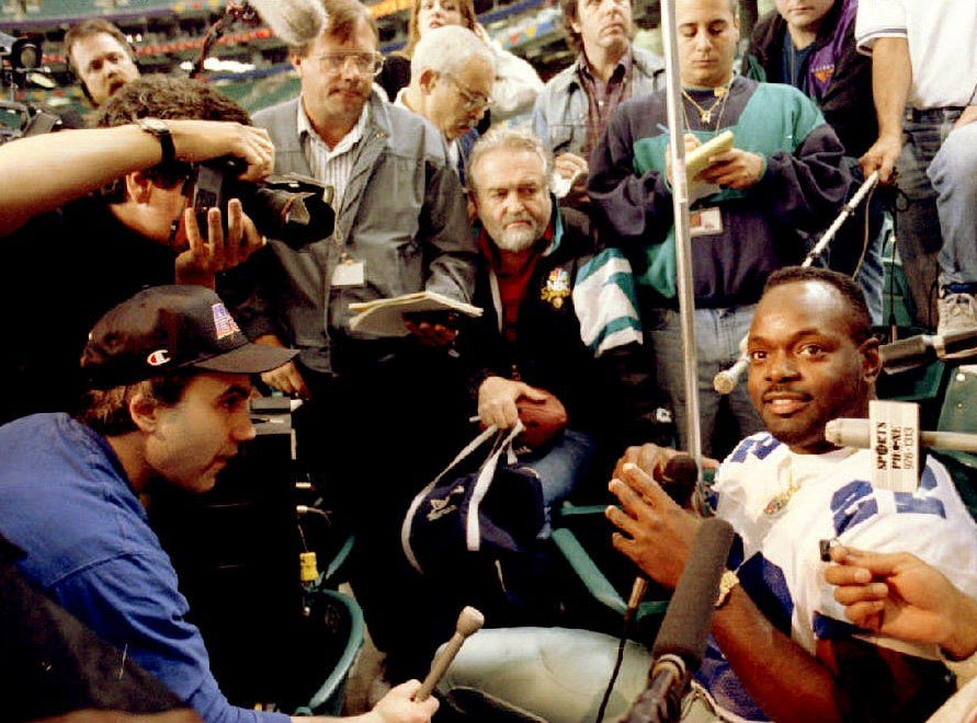 ATLANTA, UNITED STATES:  Dallas Cowboys running back Emmitt Smith(R) is surrounded by the press during media day 25 January 1994 inside the Georgia Dome in Atlanta, GA. The defending champion Cowboys will face the Buffalo Bills 30 January in Super Bowl XXVIII. (Photo credit should read ROBERT SULLIVAN/AFP/Getty Images)