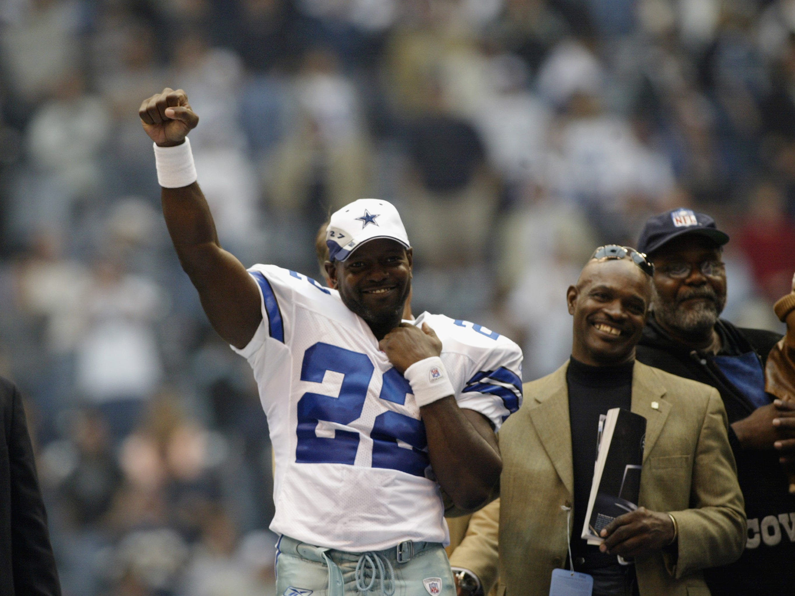 IRVING, TX - OCTOBER 27:    Emmitt Smith #22 of the Dallas Cowboys salutes the crowd as Eddie Payton, brother of Walter Payton looks on in ceremonies honoring Smith's breaking the NFL all time rushing record after their game versus the Seattle Seahawks on October 27, 2002 at Texas Stadium in Irving, Texas. The Seahawks won 17-14. (Photo by Stephen Dunn/Getty Images)
