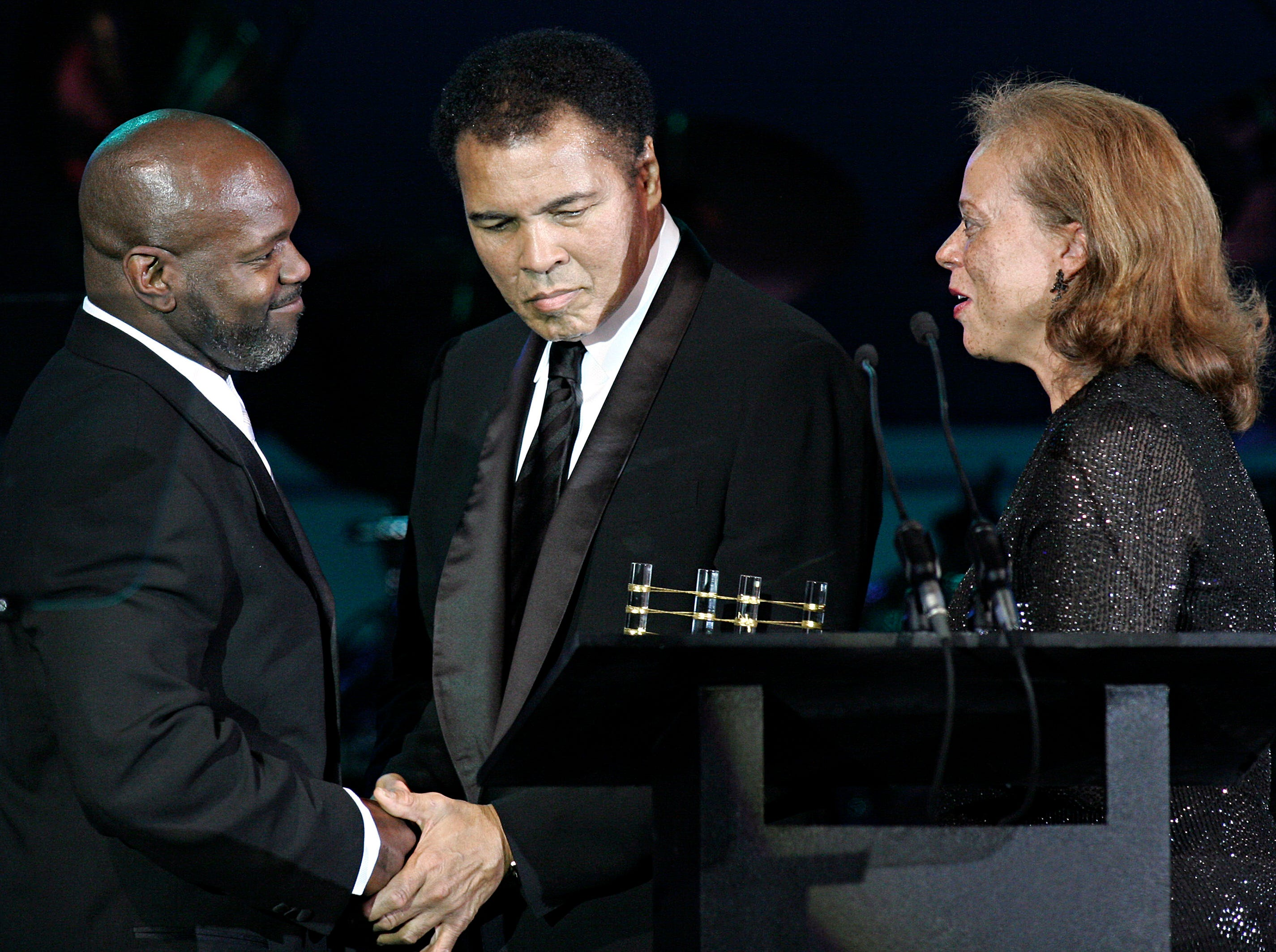 "PHOENIX - APRIL 2:  Former Dallas Cowboys running back Emmitt Smith (L) receives congratulations from former heavyweight boxing champion Muhammad Ali (C) after being award the ""Muhammad Ali Sports Achievemnet Award"" at Celebrity Fight Night XI  April 2, 2005 at Arizona Biltmore Resort & Spa in Phoenix, Arizona.  Ali's wife Lonnie (R) presented the award to Smith. The charity event raises money to battle Parkinson's disease which Ali suffers from.  (Photo by Jeff Topping/Getty Images)"