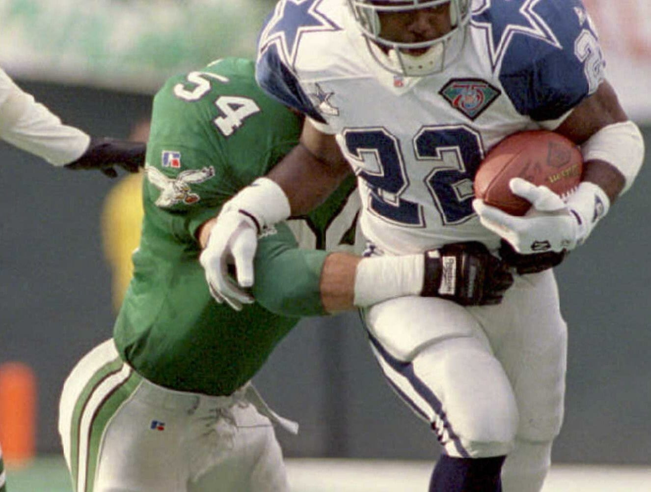 PHILADELPHIA, PA - DECEMBER 4:  Dallas Cowboys running back Emmitt Smith breaks away Philadelphia Eagles Britt Hager during the second quarter at Philadelphia's Veterans Stadium 04 December. Smith carried the ball 25 times for 91 yards and scored two touchdowns to help his team to a 31-19 victory. (COLOR KEY: Turf green)  (Photo credit should read TIMOTHY CLARY/AFP/Getty Images)