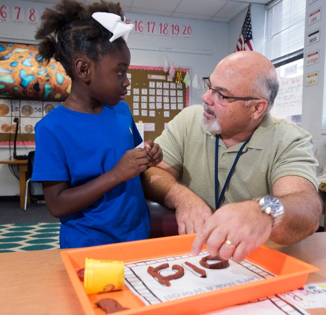 Warrington Elementary School Principal Tim Rose helps out Yquvayveya Williams with a spelling problem during his visit to her first-grade class on Friday.