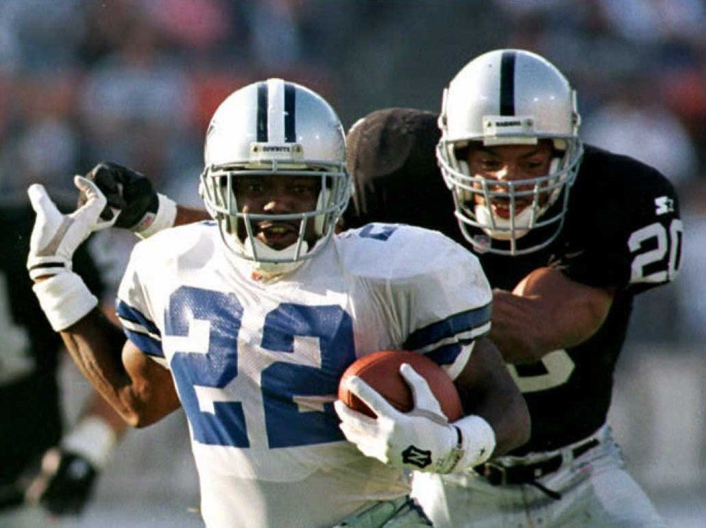 OAKLAND, UNITED STATES:  Dallas Cowboys Emmitt Smith(L) eludes a tackle from Oakland Raiders safety Derrick Hoskins(R) during the second half 19 November in Oakland, California. Smith scored three touchdowns as the Cowboys defeated the Raiders, 34-21. AFP PHOTOS (Photo credit should read JOHN G. MABANGLO/AFP/Getty Images)