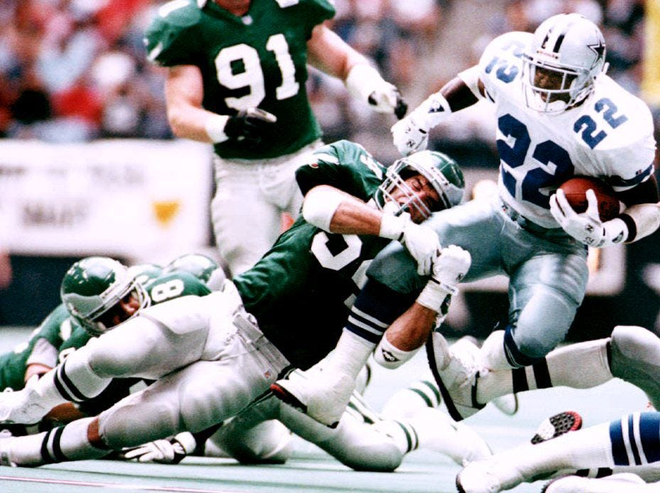 IRVING, TX - NOVEMBER 1:  Dallas Cowboys running back Emmitt Smith (22) is dragged down by Philadelphia Eagles linebacker Britt Hagar (L) after twisting his way to a first down during second quarter action 01 November. Smith gained 100 yards in the Cowboys 20-10 win over the Eagles.  (Photo credit should read TIM ROBERTS/AFP/Getty Images)