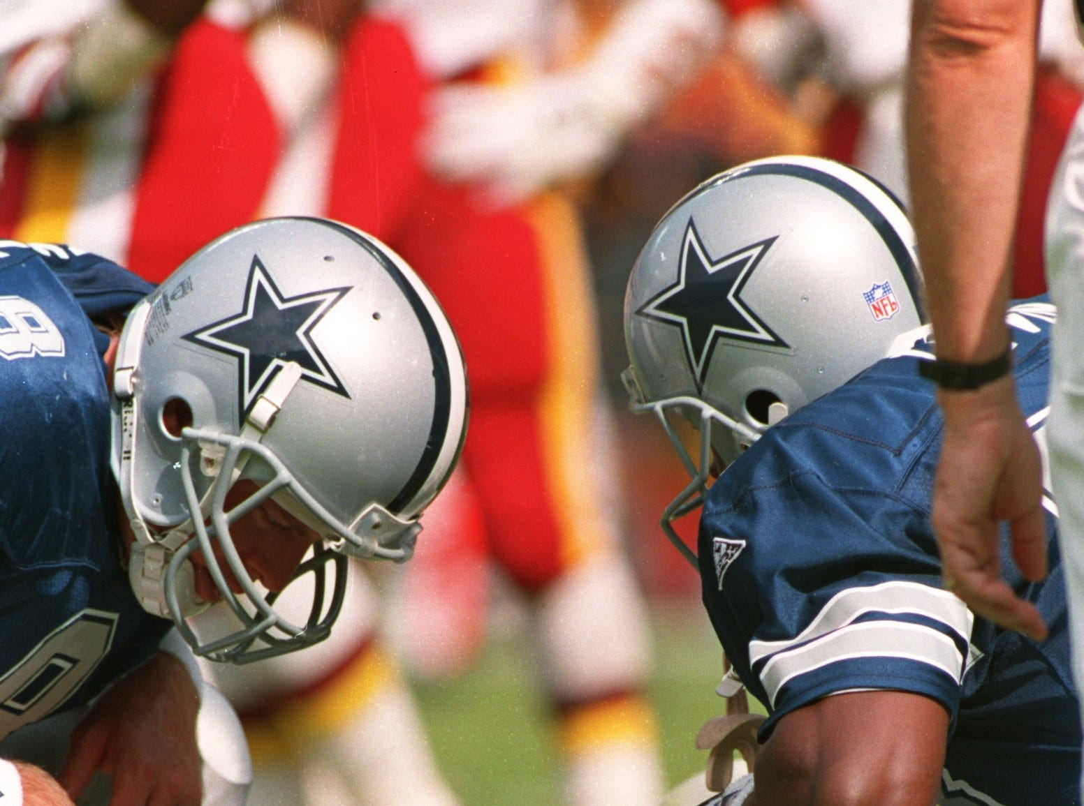 Running back Emmitt Smith #22 of the Dallas Cowboys lies injured as teammates Troy Aikman #8 and Michael Irvin #88 look on during the second quarter of game against the Washington Redskins on October 2, 1994 at RFK Stadium in Landover, Maryland.  Smith strained a hamstring and left the game. (Photo by Jonathan Daniel/Getty Images)
