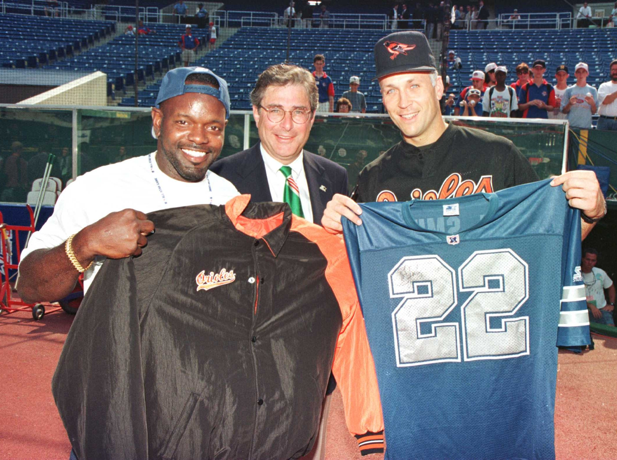 David Beckerman (middle), the CEO of Starter, watches as Emmitt Smith of the Dallas Cowboys (left) and Cal Ripken Jr. (right) of the Baltimore Orioles hold eachothers jerseys.  This was part of a jersey exchange between the two athletes before the Major League Baseball All-Star Game at Veterans Stadium in Philadelphia.  Mandatory Credit: Al Bello/ALLSPORT
