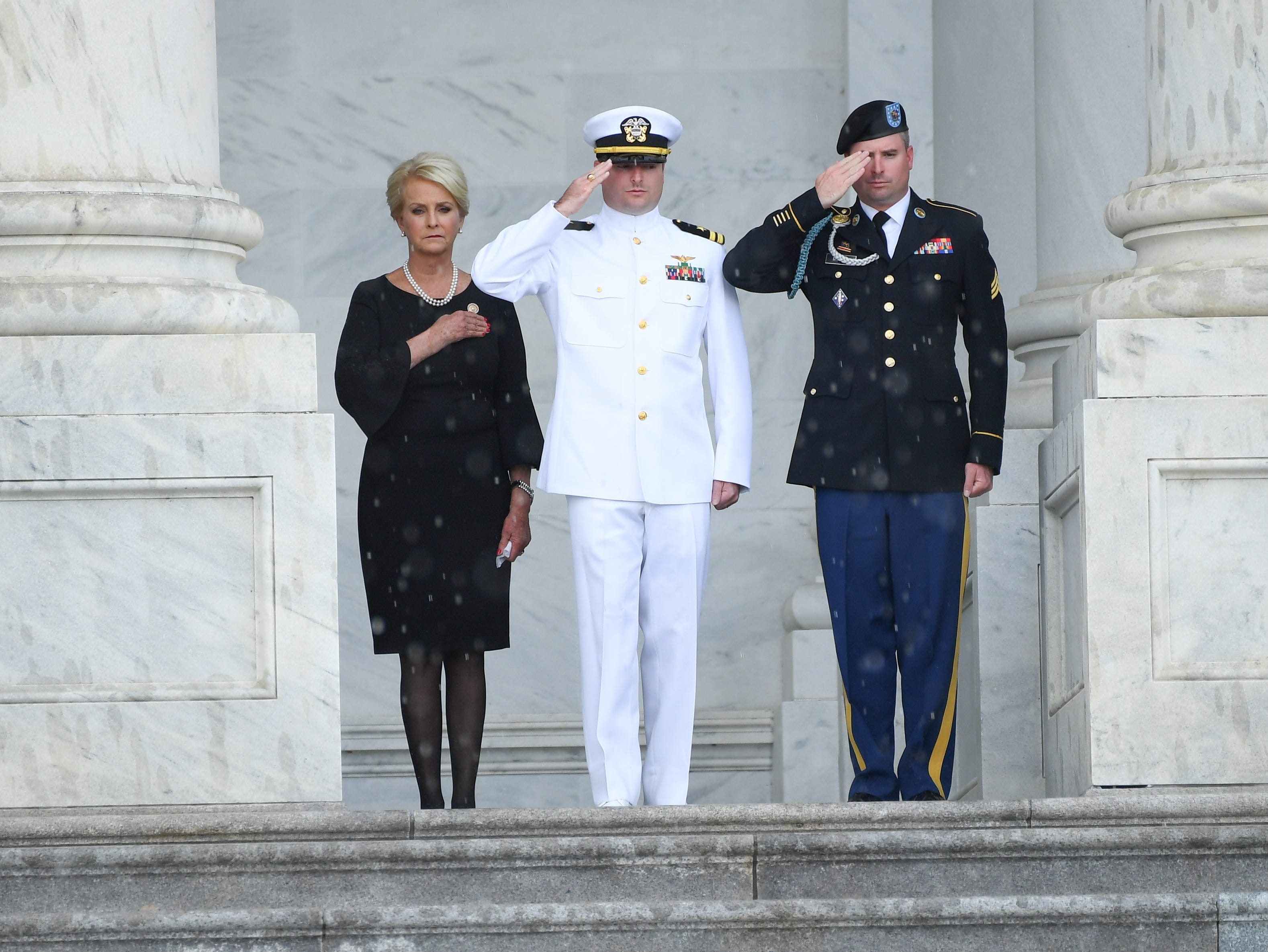 Cindy McCain, wife of Sen. John McCain, watches her husband's casket arrive at the U.S. Capitol as their two sons Jack and Jimmy McCain salute at the U.S. Capitol in Washington on Aug. 31, 2018.