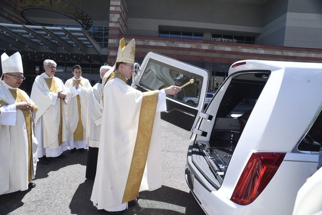Rev. Thomas J. Olmsted, bishop of the Roman Catholic Diocese of Phoenix, splashes holy water on the casket of retired Phoenix Bishop Thomas J. O'Brien after his funeral on Aug. 31, 2018.