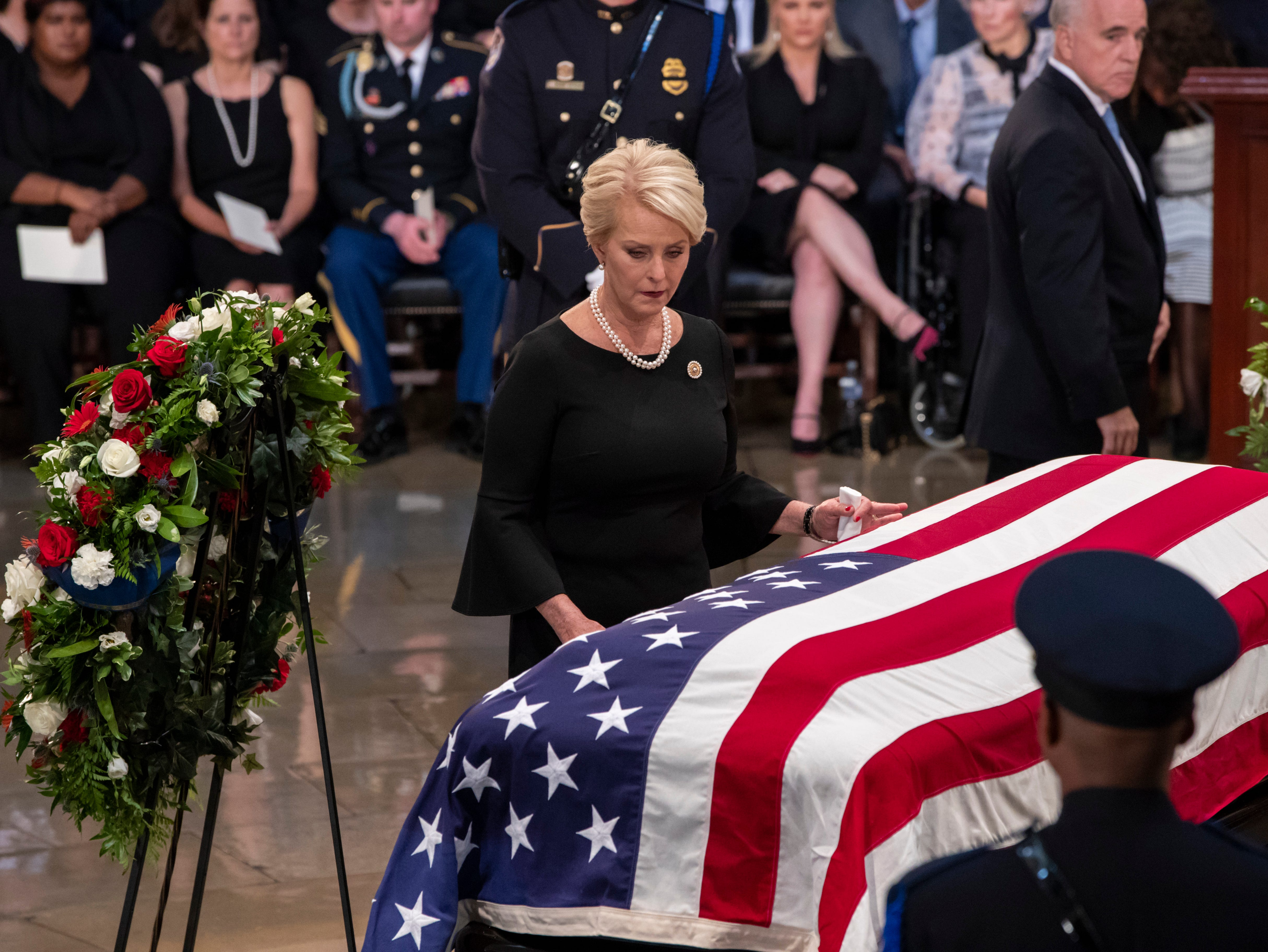 Cindy McCain, wife of Sen. John McCain, R-Ariz., touches his flag-draped casket during a farewell ceremony in the U.S. Capitol rotunda, Friday, Aug. 31, 2018, in Washington. (AP Photo/J. Scott Applewhite)